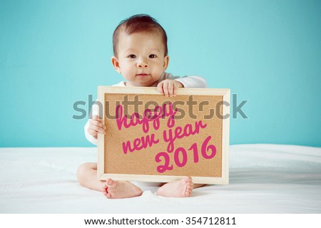 """Baby writing """"Happy New Year 2016"""" on the board, new family concept, studio shot - stock photo"""