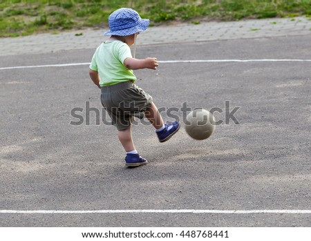 baby 2 years playing soccer ball with Dad - stock photo