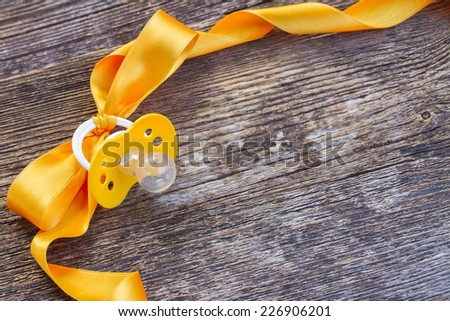 baby yellow pacifier  with ribbon frame on wooden table background - stock photo