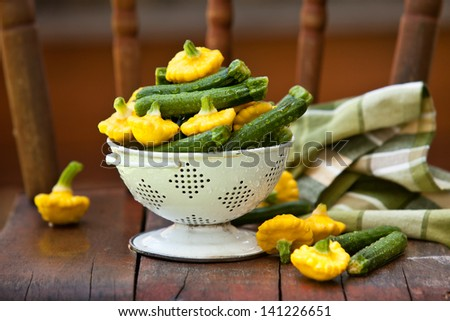 Baby Zucchini and Patty Pan Squash in white colander. Also available in vertical format. - stock photo