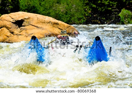 Babyboomer male rowing class III rapid on his cataraft, the hottest new boat in whitewater rafting - stock photo