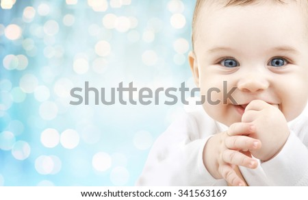 babyhood, childhood and people concept - happy baby face over blue holidays lights background - stock photo
