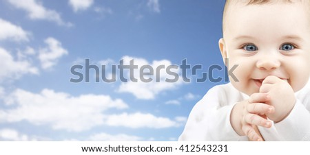babyhood, childhood and people concept - happy baby face over blue sky background - stock photo