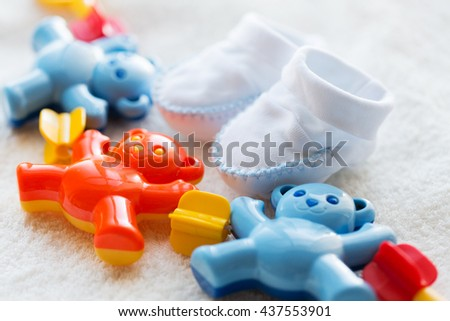 babyhood, childhood, toys, clothing and object concept - close up of baby rattle and bootees for newborn boy on towel - stock photo