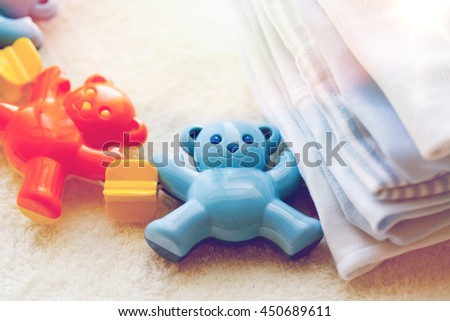 babyhood, childhood, toys, clothing and object concept - close up of baby rattle and clothes for newborn boy on towel - stock photo