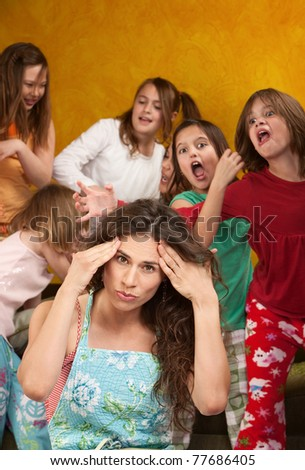 Babysitter holds head with wild little girls at a sleepover - stock photo