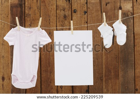 Babywear and socks and blank page on washing line - stock photo