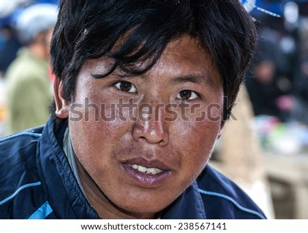 BAC HA, VIETNAM - MARCH 11, 2012: The face of a young Hmong man, who is a butcher at the market.