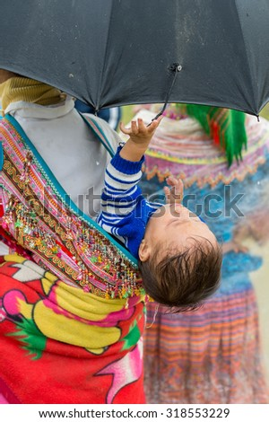 BAC HA, VIETNAM - SEP 21, 2014: Unidentified Vietnamese boy on his mother back at the Bac Ha Market, a large Sunday market with people wearing beautiful colored minorities costumes