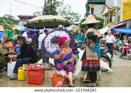 BAC HA, VIETNAM - SEP 21, 2014: Unidentified woman in tradtional ethnic dress works at the Bac Ha Market, a large Sunday market with people wearing beautiful colored minorities costumes