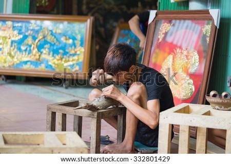 Bac Ninh, Vietnam - Sep 12, 2015: Junior craftsmen making copper handicraft products in traditional way (hand work) in Dai Bai village. Junior people are major labors in traditional works in Vietnam - stock photo