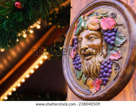 Bacchus (Dionysus) mask attached to the mulled wine stall at Christmas market in Paris (France). - stock photo