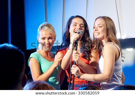 bachelorette party, karaoke, music concert and holidays concept - three happy young women or girls band singing on night club stage - stock photo