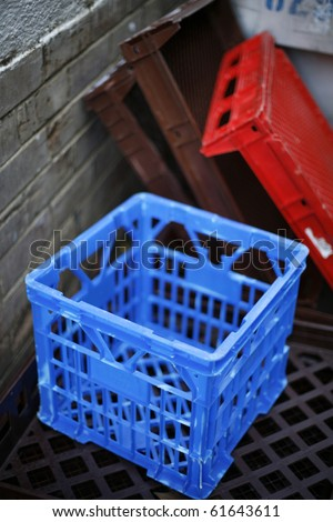 back alley in an urban city with blue plastic milk crate and bread crates in background