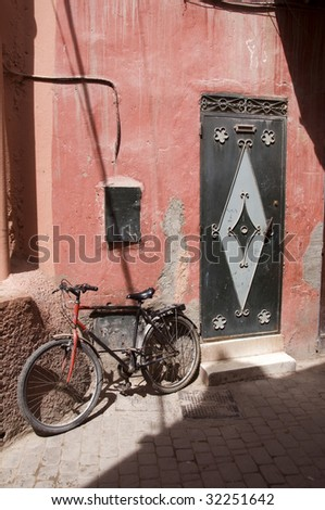 back alley street scene in old medina shopping district of casablanca morocco with detail door architecture and old bicycle - stock photo