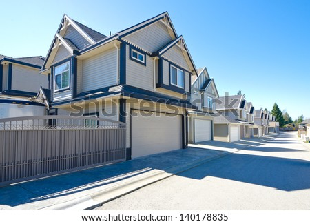 Back alley with the line of houses with double doors garages. North America. - stock photo
