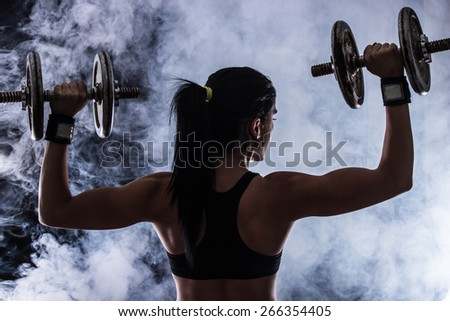 Back and hands of a young brunette sporty muscular woman working out with two metal dumbbells, isolated against black background - stock photo