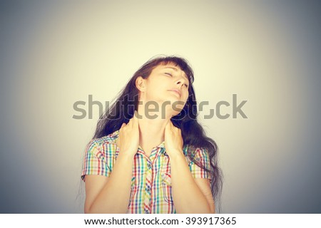 Back and spine disease.  tired woman massaging her painful neck isolated on gray background. - stock photo
