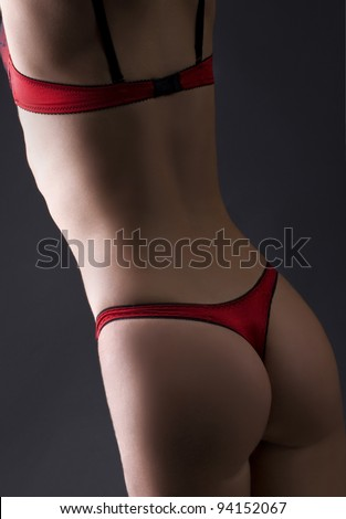 back buttock beautiful female body  in red lingerie on black background