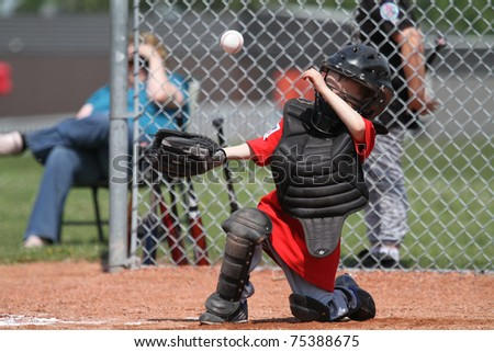 Back catcher covering mask, hiding from the ball - stock photo