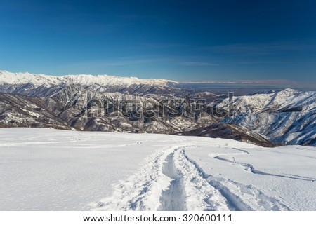 Back country ski tracks in powder snow with majestic aerial view in a winter scenery with foggy valleys below. Location: Piedmont, italian Alps. - stock photo