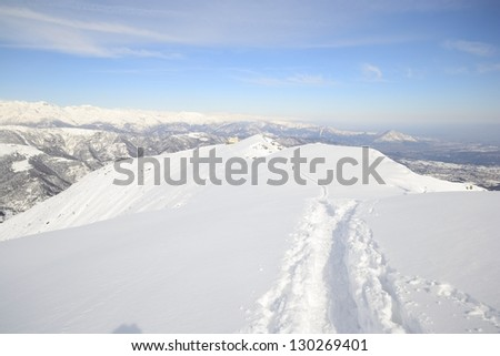 Back country ski tracks in scenic winter mountainscape with candid slope covered by thick powder snow. - stock photo