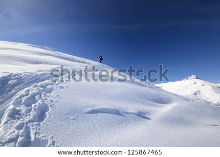 Back country skies and backpacks with avalanche safety tools in scenic winter mountain background - stock photo