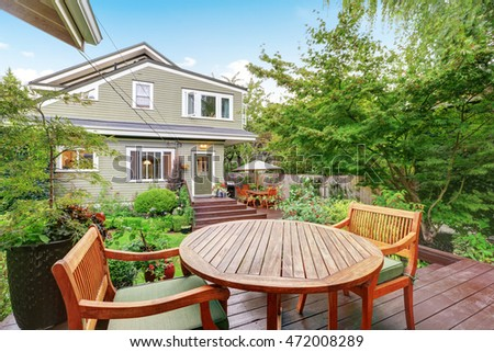 Back deck of guest house with wooden table set. Luxury house exterior. Northwest, USA
