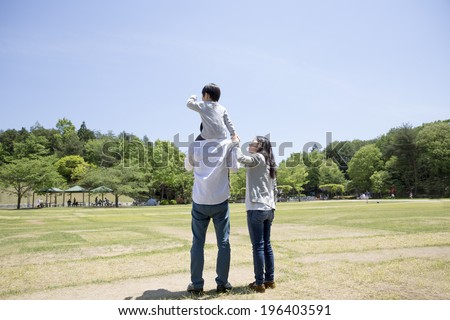 Back figure of parent and child that has a piggyback ride - stock photo