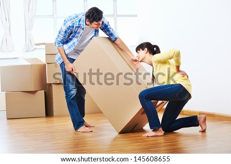back injury from carrying heavy box while moving home - stock photo