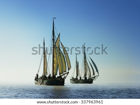 Back light image of two traditional sailing boats under sail, sailing on the ocean. Adventure concept. Reaching for new shores. - stock photo