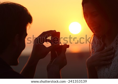 Back light of a couple proposal of marriage on the beach at sunset - stock photo
