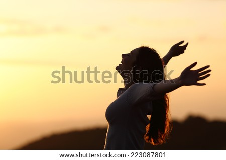 Back light of a woman breathing raising arms with a warm background - stock photo