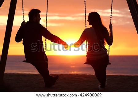 Back light portrait of a couple silhouette sitting on swing holding hands watching a sunrise on the beach with the sun in a warmth background - stock photo