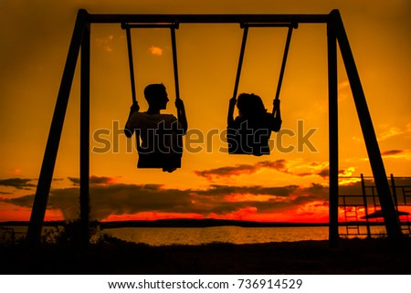 Back light portrait of a couple silhouette sitting on swing watching a sunrise on the beach with the sun in a warmth background. man and woman playing swing against sunny sunset