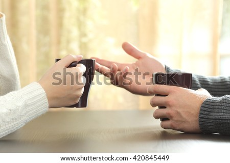 Back light profile of hands of 2 friends or couple talking holding coffee cups sitting in a table at home with a window in the background - stock photo