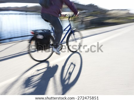 Back lit person in purple jacket cycling on bridge in bright sunshine, casting long shadow - stock photo