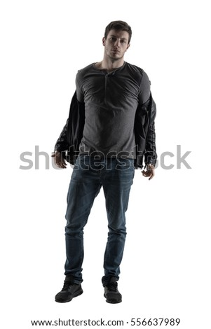 Back lit silhouette of casual man taking off jacket looking at camera. Full body length portrait isolated over white background.