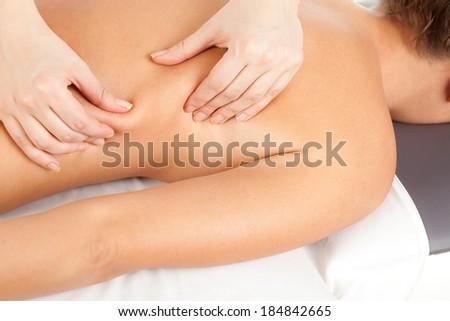 Back massage as therapy, studio shot - stock photo