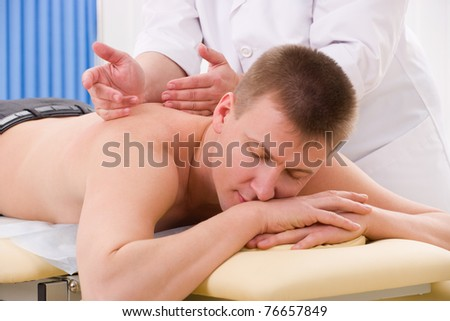 Back massage to man from doctor in her office - stock photo