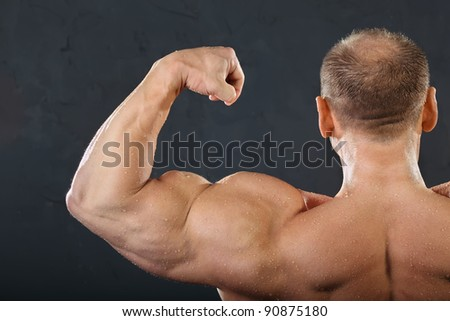 Back, neck and hand muscles of undressed tanned wet bodybuilder - stock photo