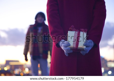 Back of a Japanese woman trying to pass a Christmas gift to man - stock photo