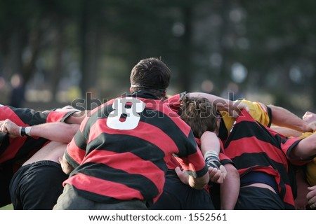 Back of a rugby scrum, powerful team work in action - stock photo