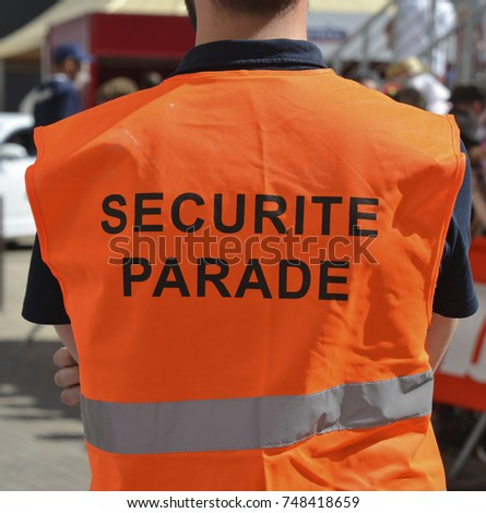 Back of a security guard in an orange uniform