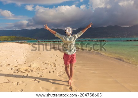 back of a sexy young man walking on the beach and celebrates his joyous life - stock photo