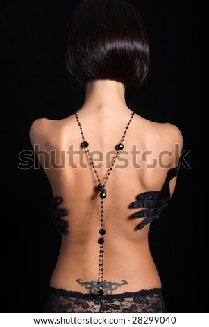 Back of a slim model in jewellery and pants. With arms on her waist - stock photo