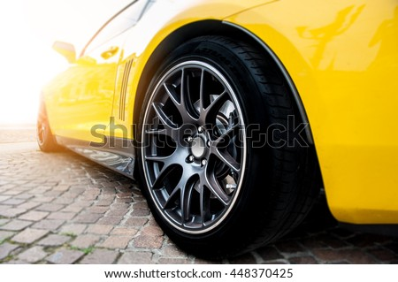 Back of a yellow modern sport car in sunset - stock photo