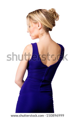 back of a young beautiful woman with upstyle blond hair wearing tight blue evening dress on her fit slim body over white studio background  - stock photo