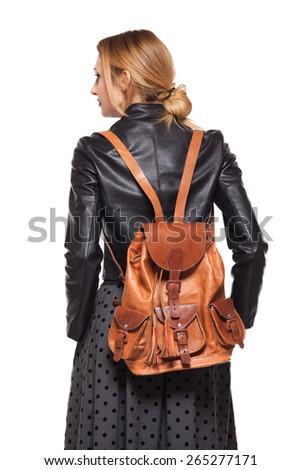 back of a young girl dressed in leather jacket with brown leather backpack on white - stock photo