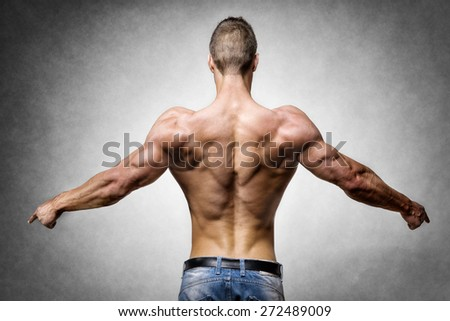 Back of a young man with well trained body, triceps, lats and rhomboid muscle and wearing a denim trousers - stock photo